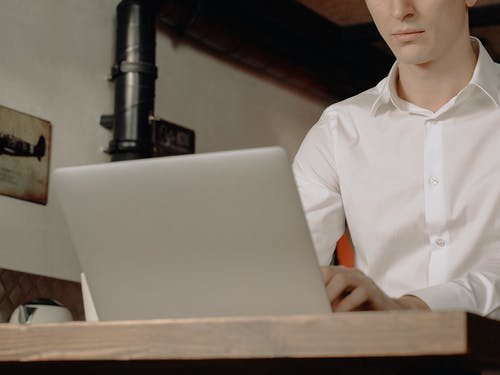 Woman in White Button Up Shirt Sitting by the Table Using Macbook