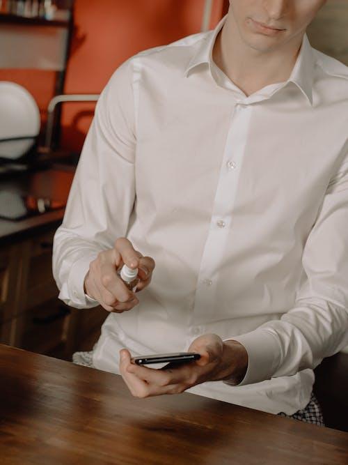 Woman in White Dress Shirt Holding Black Smartphone