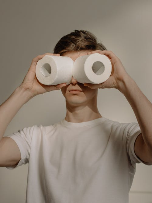 Man in White Crew Neck Shirt Holding 2 White Tissue Rolls