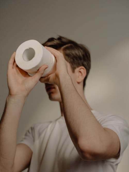 Man in White T-shirt Holding White Tissue Roll