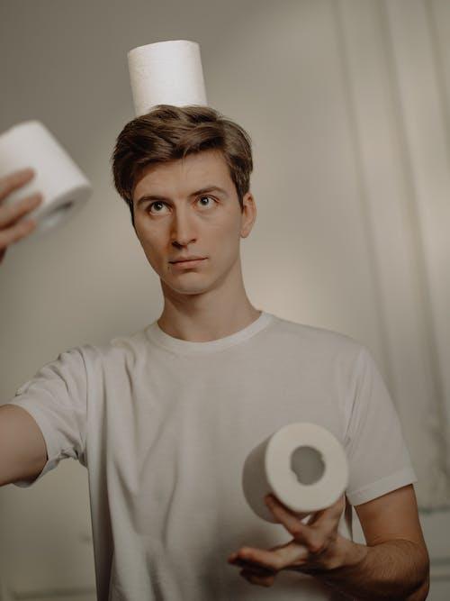 Man in White Crew Neck T-shirt Holding White Tissue Roll