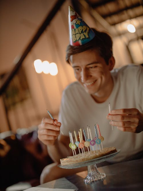 Man in White Crew Neck Shirt Holding Lighted Candles
