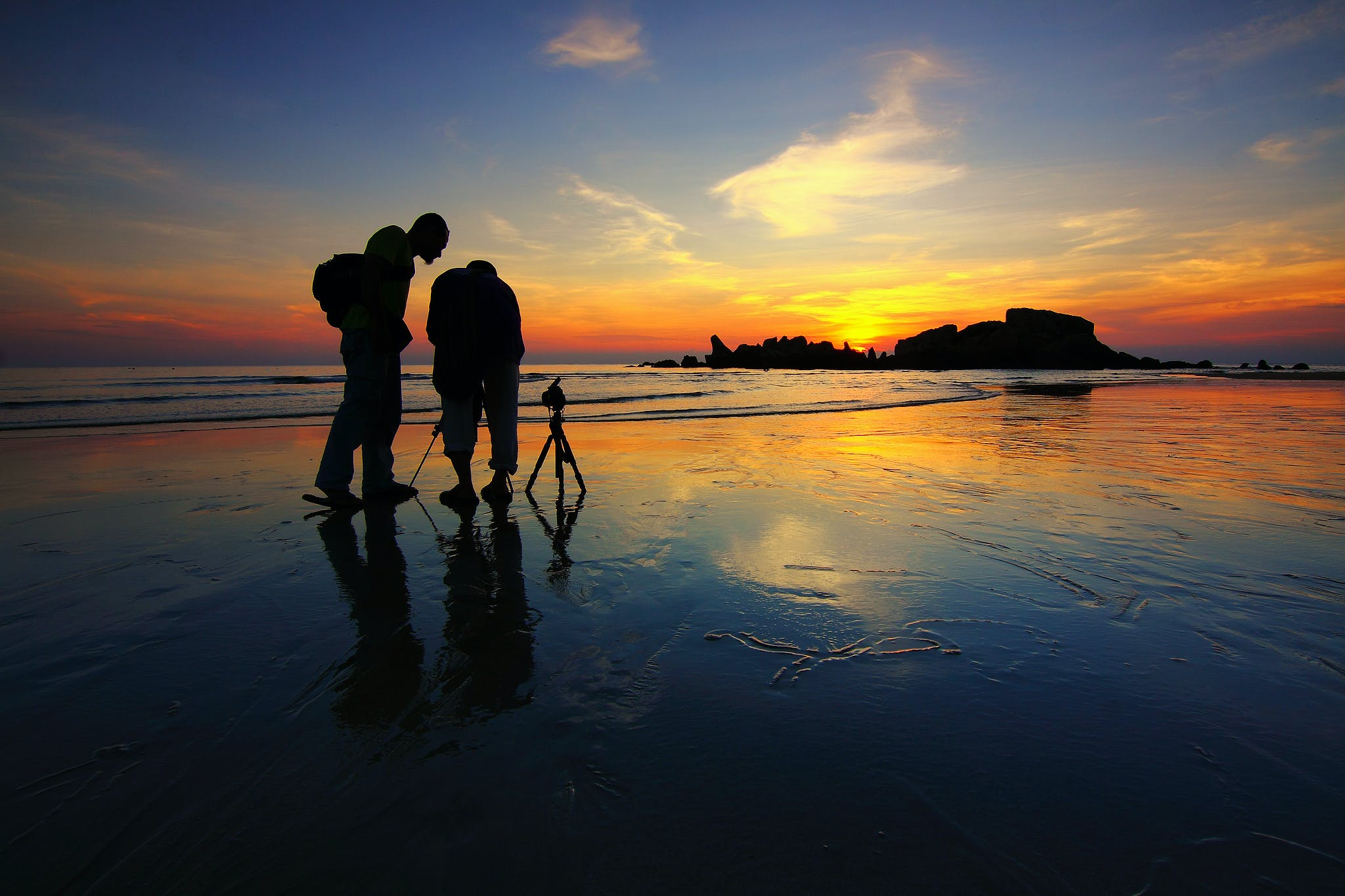 Silhouette of Two Person Taking Photo Near Shore during Golden Hour