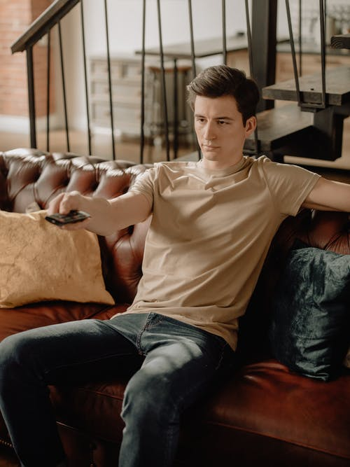 Man in White Polo Shirt and Blue Denim Jeans Sitting on Brown Couch