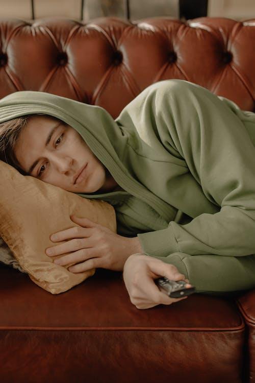 Woman in Brown Hoodie Lying on Bed