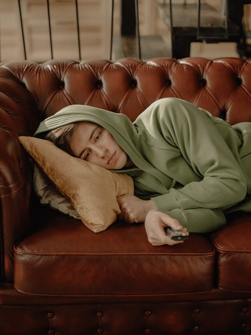 Person in Gray Robe Lying on Brown Leather Couch