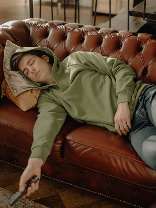 Man in Green Hoodie and Blue Denim Jeans Sitting on Brown Leather Couch