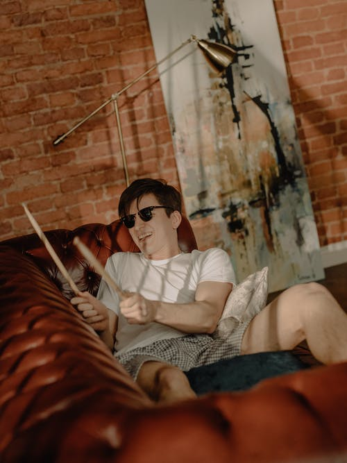 Woman in White Shirt and Black Sunglasses Sitting on Couch