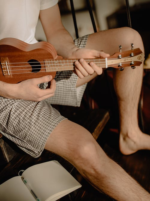 Man Playing Brown Acoustic Guitar