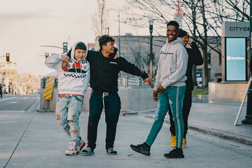 Full body of cheerful black man in casual clothing looking away while male friend hugging Asian man with bright smile