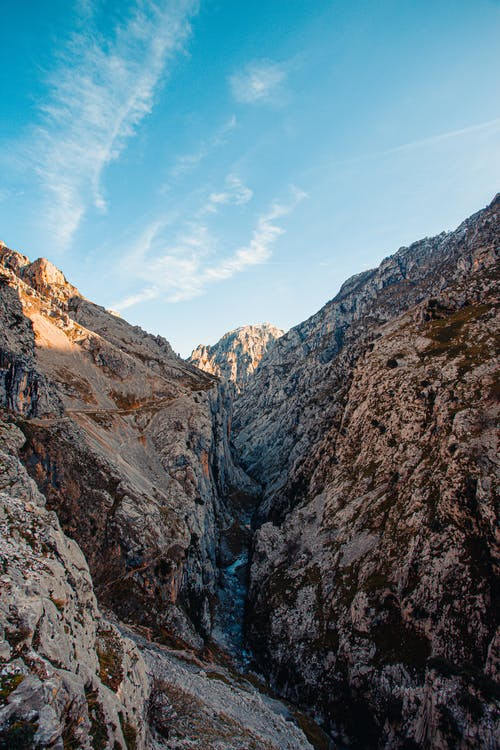From above scene view of blue sky above steep rocks and swirling mountain river in valley
