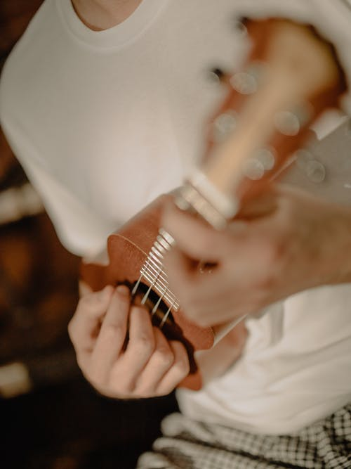 Person Playing Guitar in White Room