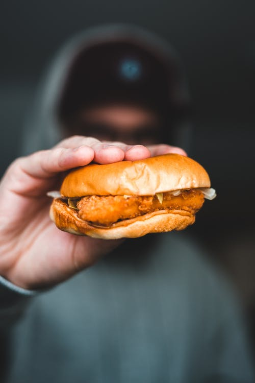 Anonymous man demonstrating burger with cutlet