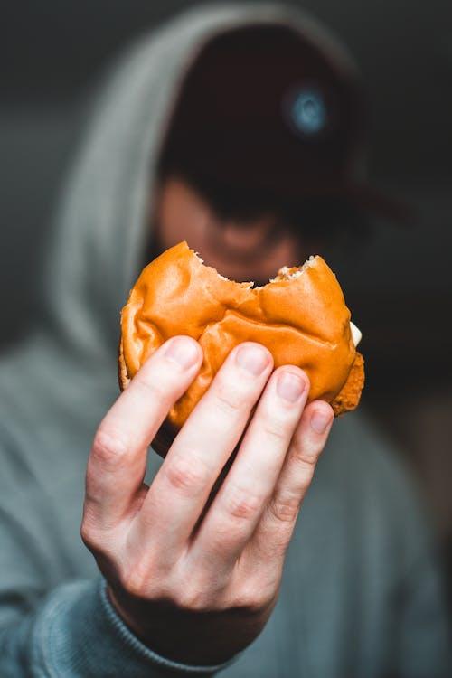 Faceless man showing bitten burger