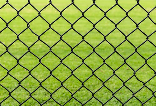 Full frame background of fence with chain link net on blurred green meadow