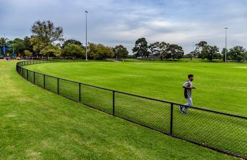 Athlete running in green stadium behind fence