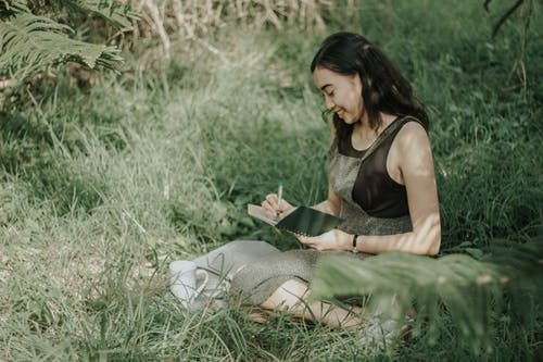 Woman in Black Tank Top and Gray Pants Sitting on Green Grass Field