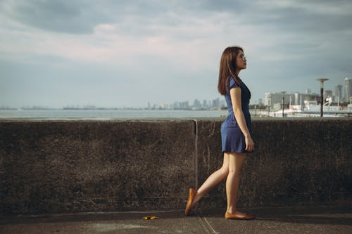 Woman in Blue Dress Standing on Gray Concrete Road