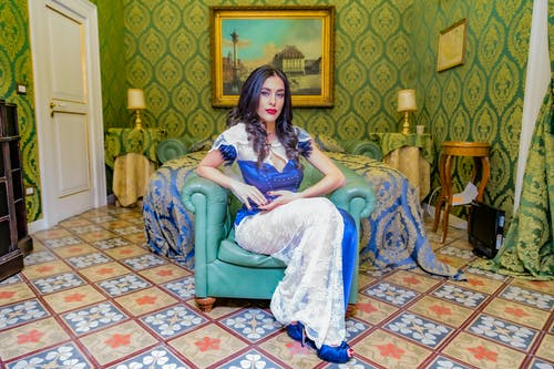 Full body brunette with red lips wearing lace blue dress with heels sitting in armchair in rich room