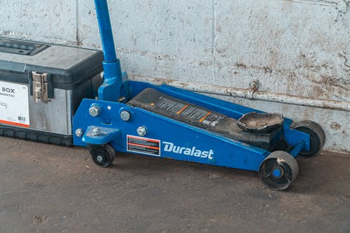 Blue Tool Jack Lift Car For Repair Beside A Tool Box