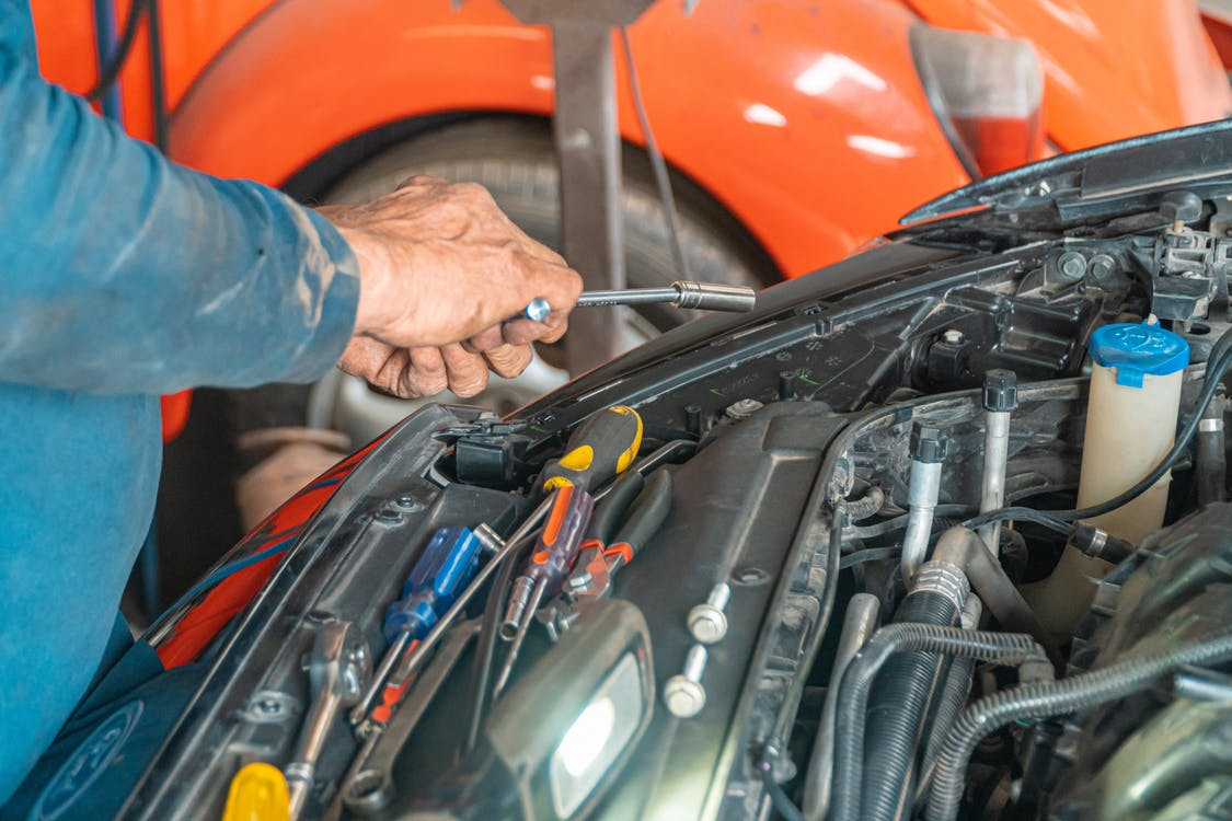 A mobile vehicle mechanic servicing a vehicle and replacing a part