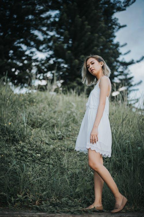 Woman in White Sleeveless Dress Standing Near Green Grassland