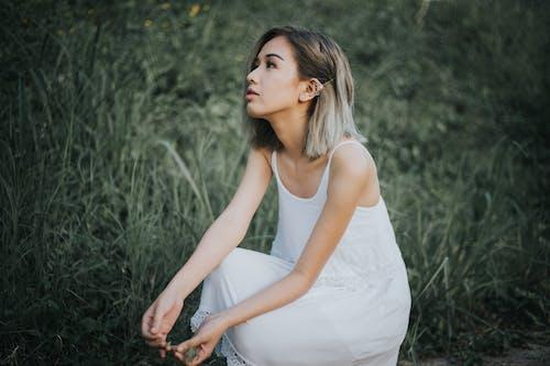 Woman in White Tank Dress Sitting on Grass Field