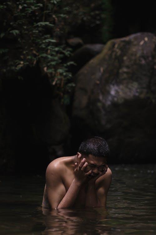 Topless Man Sitting on Rock Near Body of Water