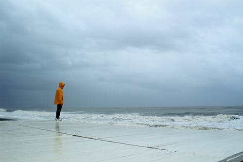 Person in Yellow Jacket and Black Pants Standing Near The Sea