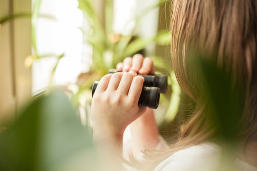 Woman Holding Black Binoculars