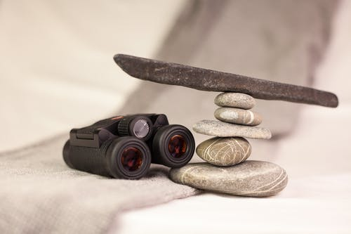Black Binoculars on White Textile Near Stones