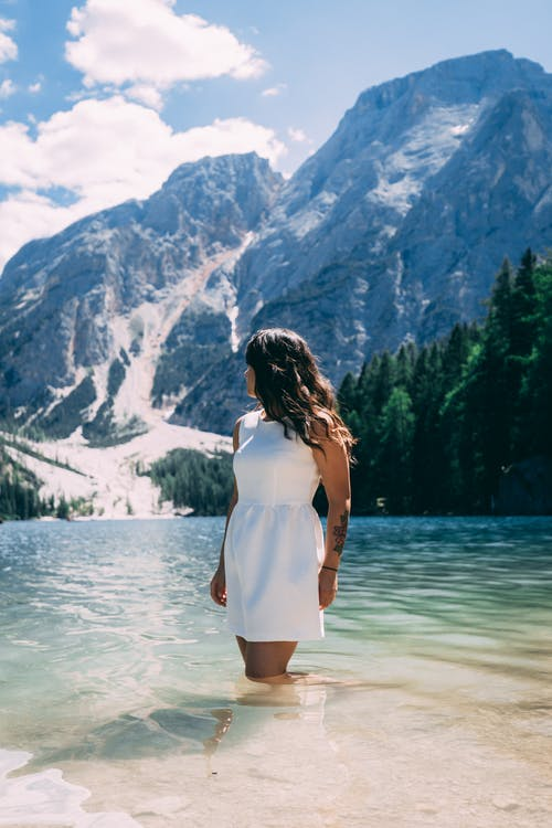 Woman in White Dress Standing on Water Near Snow Covered Mountain