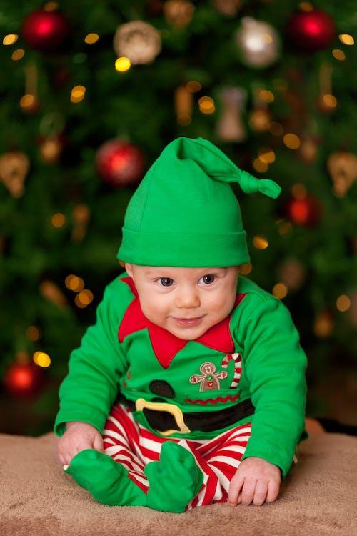 Baby Wearing Green Elf Costume Sitting on Brown Rug