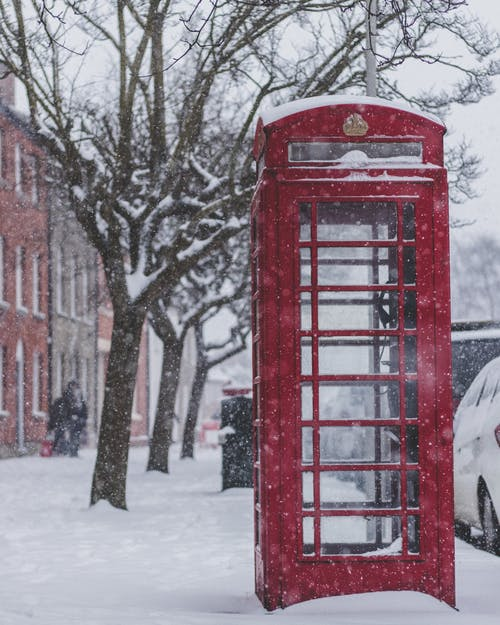 Red Telephone Booth on Snow Covered Ground