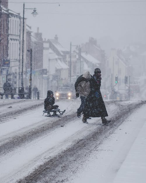 People Crossing A Snow Covered Street