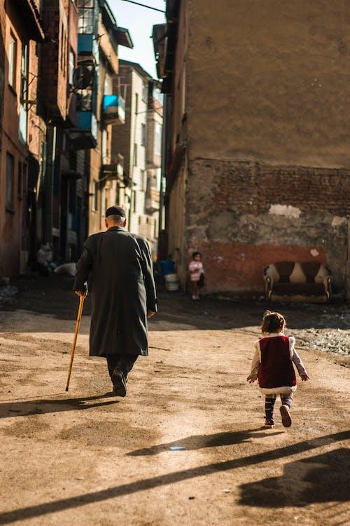 Man in Black Robe Holding Stick Walking on Street