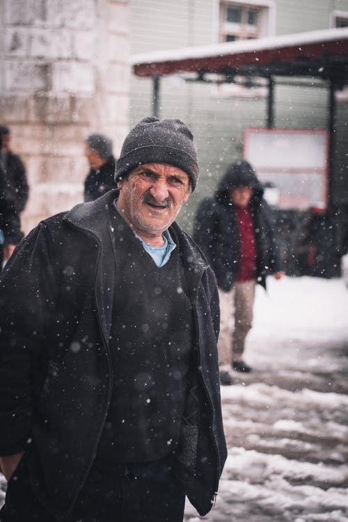 Man in Black Jacket and Knit Cap Standing on Snow Covered Ground