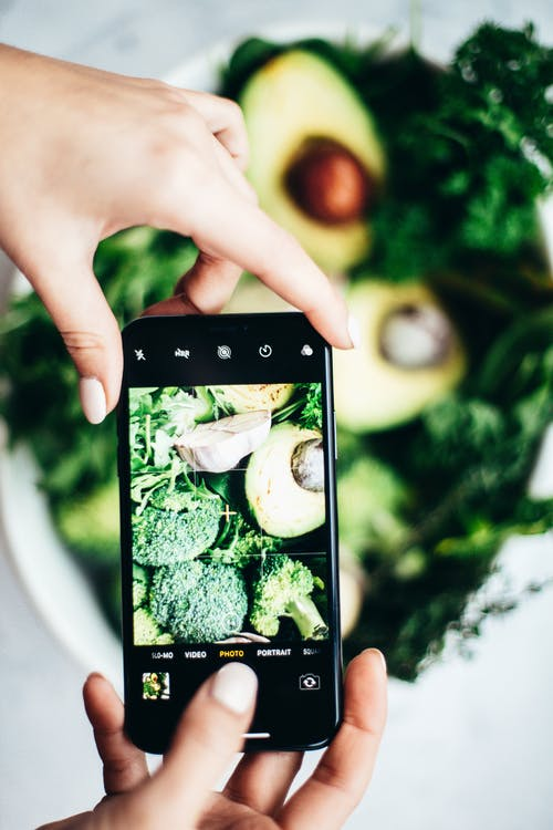 Person Taking A Picture Of Broccoli On Table