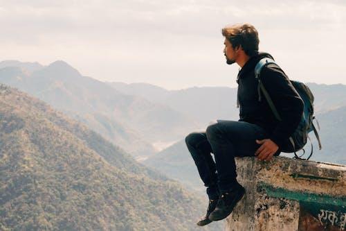 Risky traveler on stone above valley