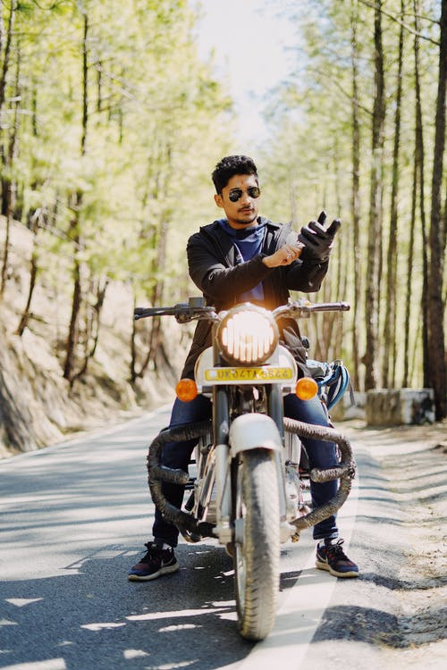 Full body ethnic man in sunglasses wearing gloves while sitting on bike in sunny forest