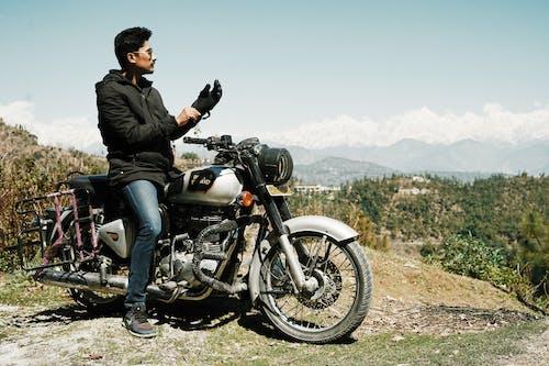 Cool biker on high hill observing landscape