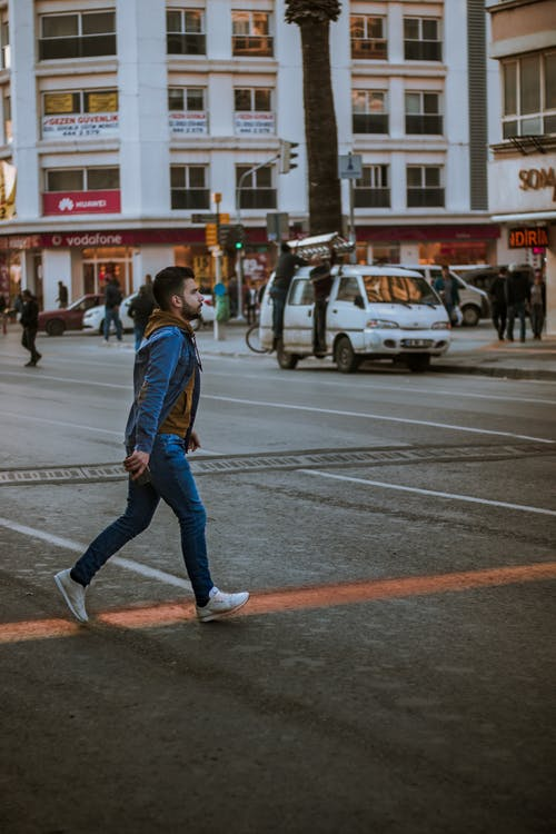 Woman in Blue Denim Jacket and Blue Denim Jeans Walking on Pedestrian Lane