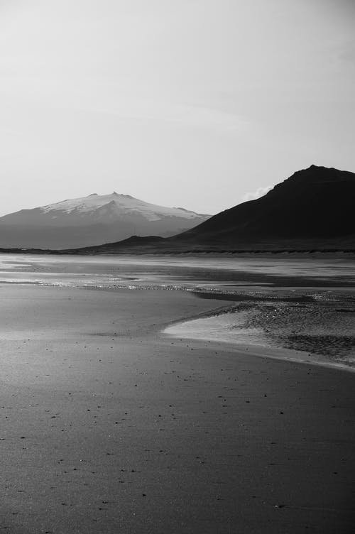 Black and white smooth sandy beach with calm sea waves and dark hills on background