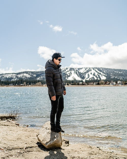 Man in Black Jacket Standing on Brown Rock Near Body of Water