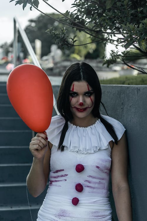 Young woman wearing spooky Halloween costume of clown with red balloon standing on street