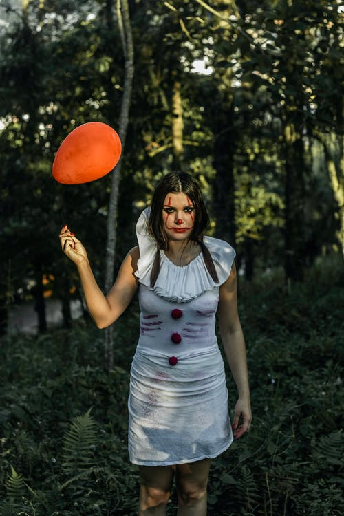 Woman in spooky costume with balloon in woods