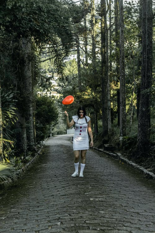 Spooky woman with balloon on pathway