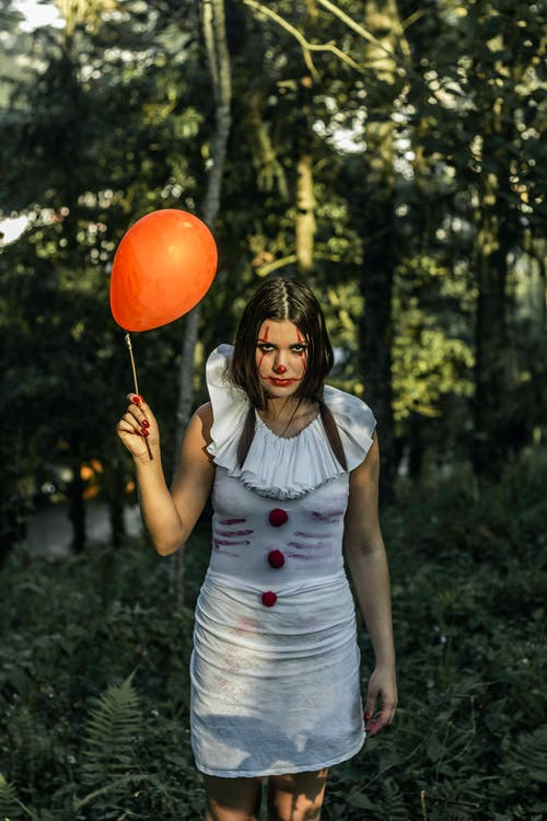 High angle of monstrous woman in white dress and with clown makeup holding red balloon standing in forest