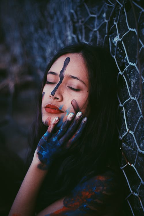 Alluring woman smeared with dark paint