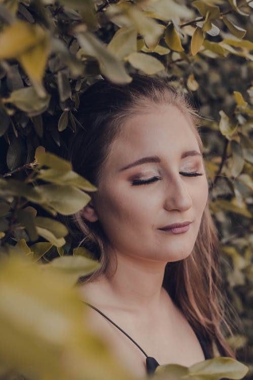 Young dreamy female with makeup on eyelids and lips standing with closed eyes near tree with leaves in garden in fall